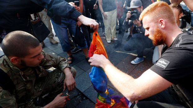 Ukrainian ultra nationalist activists burn a rainbow flag as they protest against the annual Gay Pride parade.