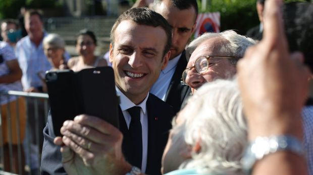 Emmanuel Macron poses for a selfie after voting in the final round of parliamentary elections. The new French president ...