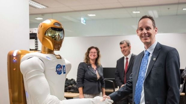 Woodside Energy chief technology officer Shaun Gregory shakes the Robonaut's hand at Woodside's Perth office.
