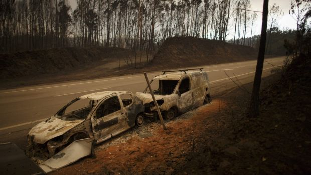 Burnt cars on the side of the road after a wildfire took dozens of lives on June 18.