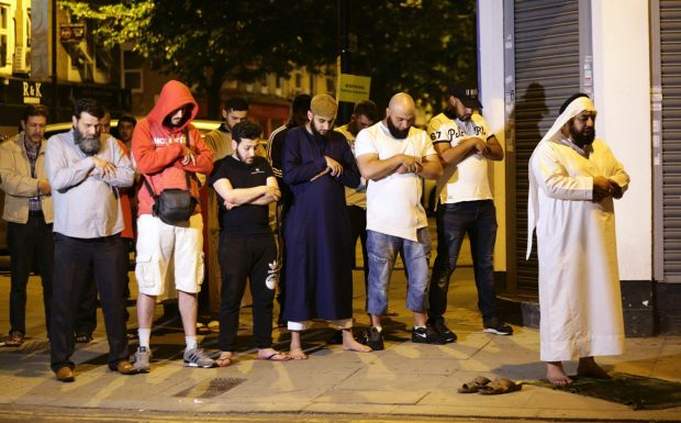 Local people observe prayers at Finsbury Park where a vehicle struck pedestrians in north London.