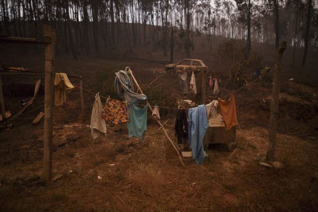 Clothes are hanging for drying next to a burned car after a wildfire took dozens of lives near Castanheira de Pera, Portugal.