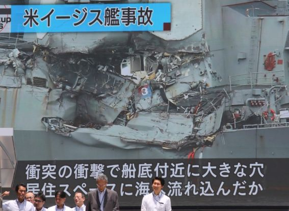 A screen shows a news program reporting about a collision between a US destroyer and a container ship off Japan, in ...