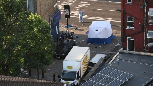 A police forensics officer examines the scene at Finsbury Park, where one person was killed and eight were injured in a ...