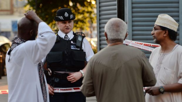 A police officer talks to Finsbury Park locals near the scene where a van hit pedestrians.