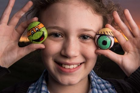 Keira Sen, 9, with some of the rocks she has painted ready to be 'dropped' at a local park.