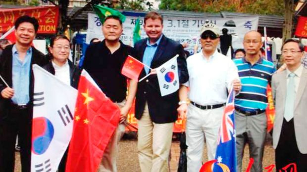 Craig Laundy (holding Chinese and Korean flags) and Yang Dongdong (far right) at a protest against Shinzo Abe's visit to ...