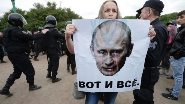 A woman holds a poster depicting Russian President Vladimir Putin with the slogan 'This is it' during an anti-corruption ...
