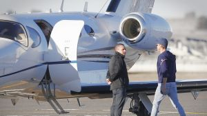 Pixie waits in the doorway as her father Oliver Curtis boards a jet for his return to Sydney.