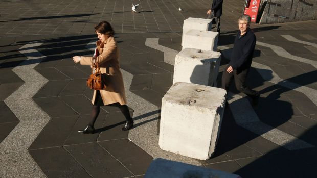 City workers pass the bollards at Queensbridge Square.