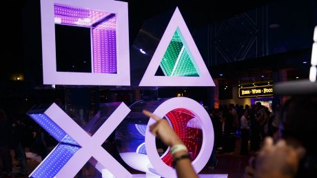An attendee points past a Sony Corp. PlayStation logo before a Sony event ahead of the E3 Electronic Entertainment Expo ...