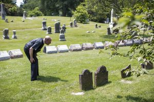 Rev Meeter reads a gravestone in the plot of land that his church as sold to Green-Wood cemetery.