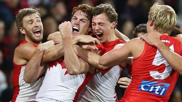 Gary Rohan celebrates with team mates after kicking a goal to win the match during the round 14 AFL match between the ...
