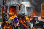 A masked demonstrator walks near a flaming truck, seized and set on fire by demonstrators, during an anti-government ...