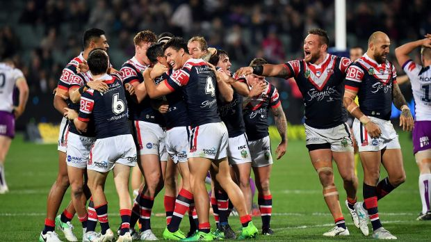 Late drama: Mitchell Pearce is mobbed by teammates after slotting home the winning field goal in golden point.