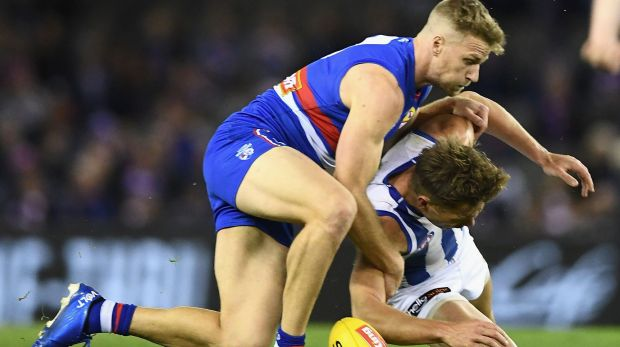 Talking point: Shaun Higgins of the Kangaroos is tackled by Jake Stringer of the Bulldogs.