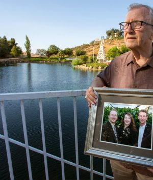 In this Friday, June 23, 2017 photo, Frank Kerrigan holds onto a photograph of his three children John, Carole, and ...