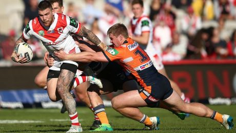 SYDNEY, AUSTRALIA - JUNE 25: Josh Dugan of the Dragons is tackled during the round 16 NRL match between the St George ...