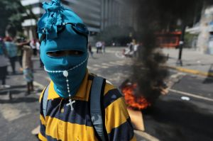 A youth wearing a mask and rosary stands near a burning barricade  in Caracas.