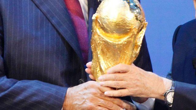 Sheikh Hamad bin Khalifa Al-Thani, Emir of Qatar (left) is presented with the World Cup trophy by former FIFA president ...