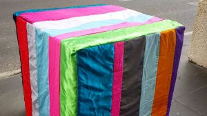 A guerilla artist has sewn a coloured cover for a temporary concrete bollard at Southern Cross Station.