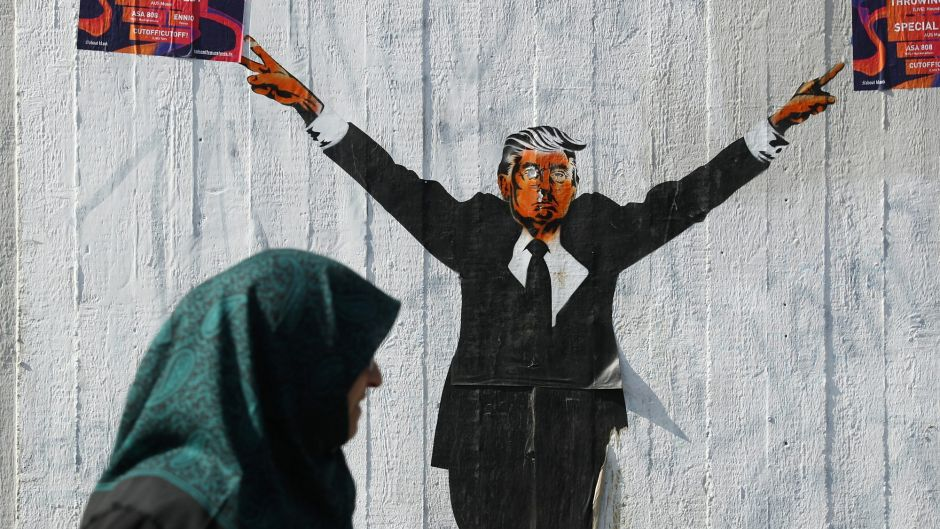 BERLIN, GERMANY - JUNE 27: A Muslim woman walks past a street artist's rendition of U.S. President Donald Trump on June ...