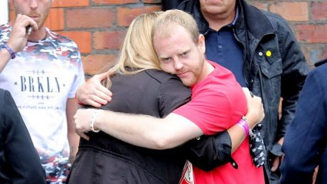 Family members hug after being told charges have been laid against six people over the Hillsborough tragedy.