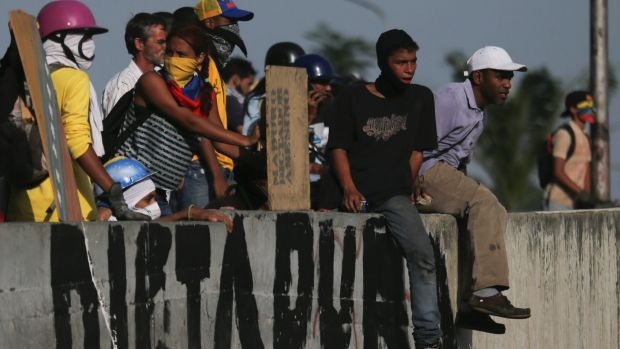 "Anti-government protesters take positions behind a road wall covered with the Spanish word ""Dictatorship"" in Caracas."