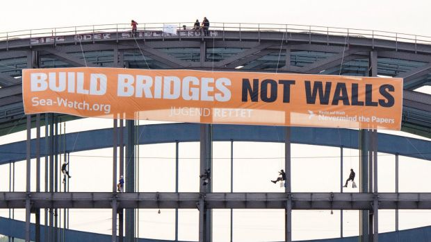 Activsts of the refugee support group SeaWatch attach a poster 'Build bridges not walls' to a bridge over the river Elbe ...