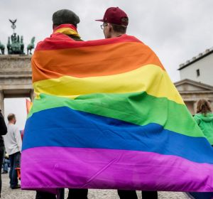 Men with rainbow flags stand in front of the Brandenburg Gate to celebrate the legalisation of same-sex marriage in ...