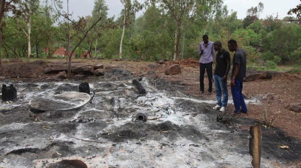 Locals look at the burnt Campement Kangaba, a resort popular with foreigners near Bamako, after it was attacked by ...
