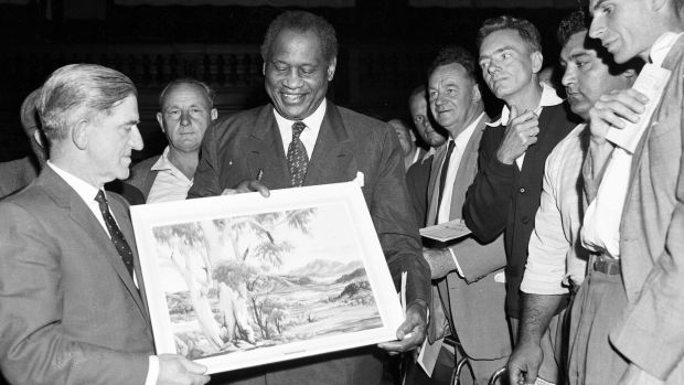 Robeson is presented with an Albert Namatjira painting during a mass meeting of waterside workers at Sydney Town Hall on ...