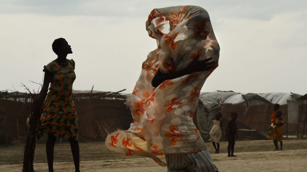 A woman walks along a road as the rains come inside the United Nations' Bentiu Protection of Civilians site, home to ...