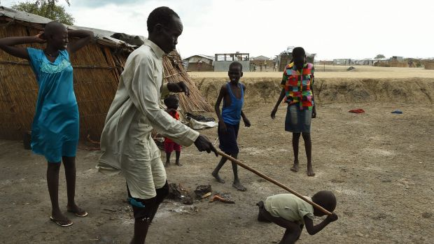 James Tut, 64 (2nd from left), who became blind in 2005, is led by a child inside the UN Bentiu Protection of Civilians ...
