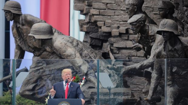 President Donald Trump speaking in Krasinski Square, back dropped by the monument commemorating the 1944 Warsaw Uprising.
