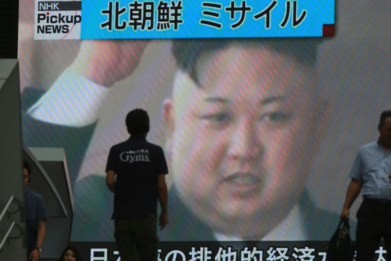 People walk in front of an image of North Korean leader Kim Jong Un shown on a large screen as a TV news reports the ...