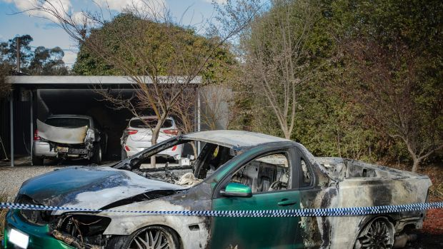 Police examine a property in Kambah after shots were fired and three vehicles were torched in July.