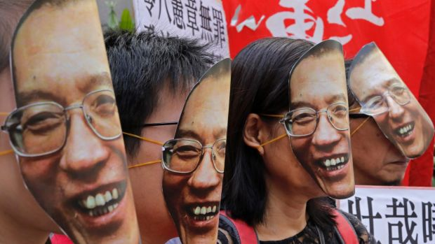 Protesters wear masks of Chinese Nobel Peace laureate Liu Xiaobo during a demonstration demanding his release outside ...