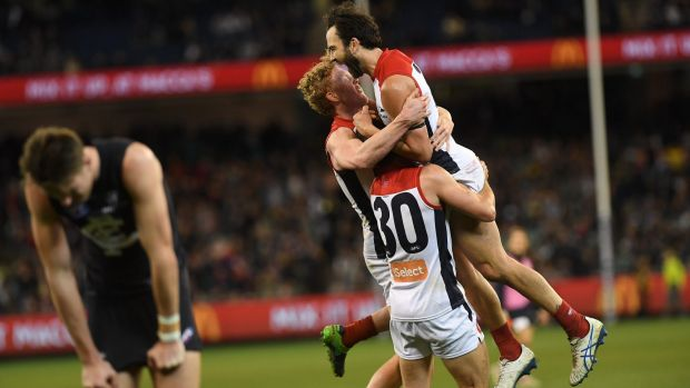 In the mix: Melbourne players after their hard-fought comeback win over Carlton.
