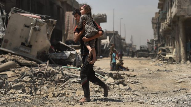 An Iraqi male runs barefoot carrying his sister as they escape from  the front lines in West Mosul a week ago.