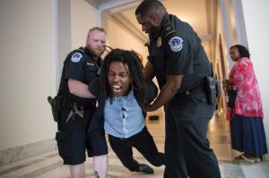 A demonstrator is taken into custody by U.S. Capitol Police as activists protest against the Republican health care bill ...