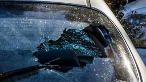 A car sitting on the property's front lawn had been damaged by gunfire.
