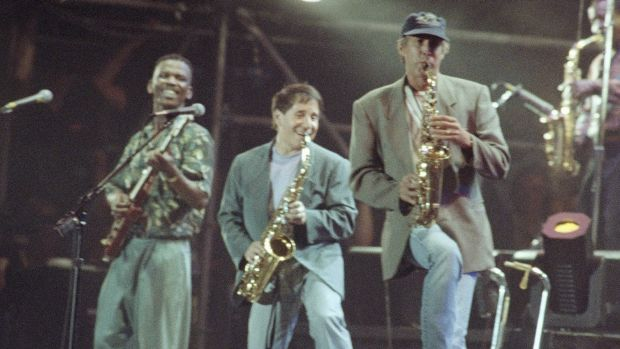 Paul Simon, centre, with lead guitarist Ray Phiri, left, and actor-comedian Chevy Chase on the saxophone, New York, 1991.