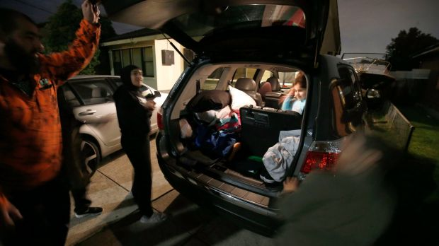 Dallas residents Hassan and Helen Halwani and their four children pack their car to flee Dallas late Thursday night.