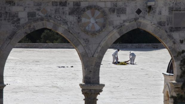 Israeli police forensic experts inspect the body of a Palestinian at the scene of an attack in the al-Aqsa Mosque ...