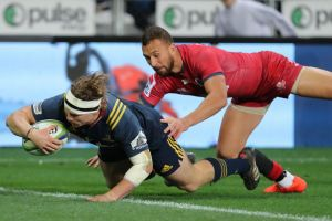 James Lentjes of the Highlanders evades the tackle of the Reds' Quade Cooper to score at Dunedin.
