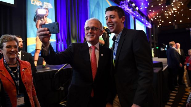 Prime Minister Malcolm Turnbull takes a selfie with a young party member at the LNP state conference in Brisbane on Saturday