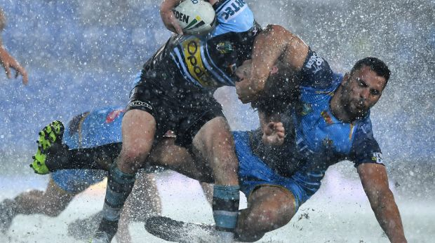 Big wet: Chad Townsend is tackled by Ryan James in atrocious conditions at CBUS Stadium on the Gold Coast.