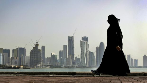 A woman walks in front of the city skyline in Doha, Qatar's capital.