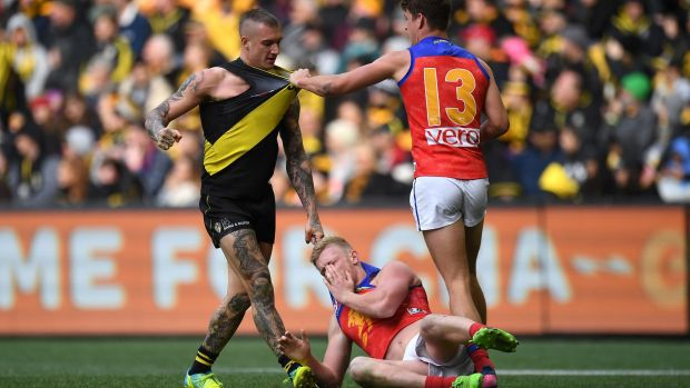 Brisbane's Nick Robertson hits the ground after an incident involving Tiger Dustin Martin as Jarrod Berry comes in to ...